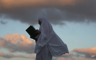 A Palestinian girl reads the Quran in the first of Shaban month in the West Bank city of Nablus, Palestine on June 1, 2014. (AP Photo/Nasser Ishtayeh)