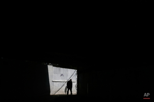 A man walks under a bridge in central Athens on Monday, March 30, 2015. Greece and its international creditors are still struggling to agree on a list of economic reforms that are deemed necessary for the country to unlock emergency funds and stay afloat. (AP Photo/Petros Giannakouris)