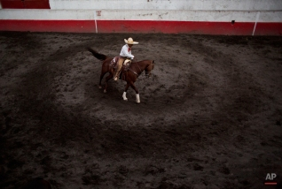 In this Feb. 26, 2015 photo, a charro warms up his horse by practicing circles outside the arena during a charreada between teams composed of the best charros from 27 Mexican states in Mexico City. (AP Photo/Rebecca Blackwell)