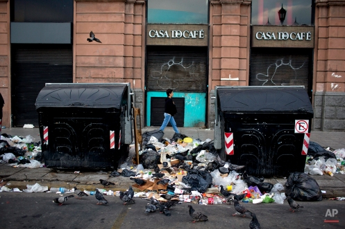 A woman walks near garbage during a strike in Buenos Aires, Argentina, Tuesday, March 31, 2015. (AP Photo/Natacha Pisarenko)