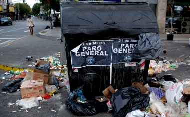 """Garbage litters a street, surrounding a dumpster with posters that read in Spanish; """"31st of March, National Strike,"""" near the Constitucion train station during a transportation strike in Buenos Aires, Argentina, Tuesday, March 31, 2015. (AP Photo/Natacha Pisarenko)"""