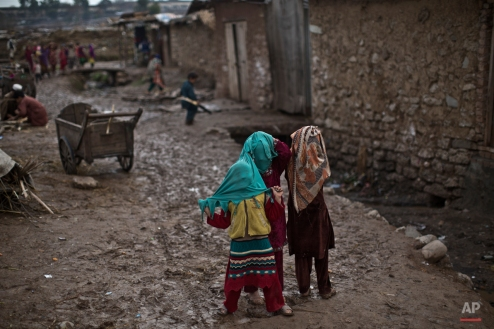 Girls cover their faces with a head scarf while playing in a slum home to Afghan refugees and internally displaced Pakistanis from tribal areas on the outskirts of Islamabad, Pakistan, Thursday, Feb. 19, 2015. (AP Photo/Muhammed Muheisen)