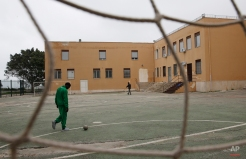 A migrant plays with a soccer ball at the migrants temporary reception center 'Umberto I', in Siracusa, Italy, Tuesday, March 24, 2015. The structure, a former school, hosts immigrants both on temporary basis and for longer periods, when needed, since 2012. (AP Photo/Luca Bruno)