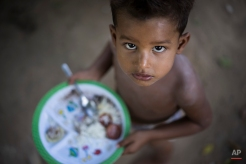 A boy looks at the camera as he eats his lunch on the shore of the polluted Jacare River in the Mandela slum of Rio de Janeiro, Brazil, Wednesday, March 4, 2015. The environmentalist and human rights organization Rio de Paz organized a press tour to the area to speak with residents who are asking the government to clean up the river and invest in recreational areas. The Jacare River flows into Guanabara Bay, where next year's Olympic sailing events are to be held. (AP Photo/Felipe Dana)