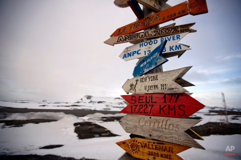 In this Jan. 20, 2015 photo, wooden arrows show the distances to various cities near Chile's Escudero station on King George Island, Antarctica. Thousands of scientists come to Antarctica for research. There are also non-scientists, chefs, divers, mechanics, janitors and the priest of the worldÌs southernmost Eastern Orthodox Church on top of a rocky hill at the Russian Bellinghausen station. (AP Photo/Natacha Pisarenko)