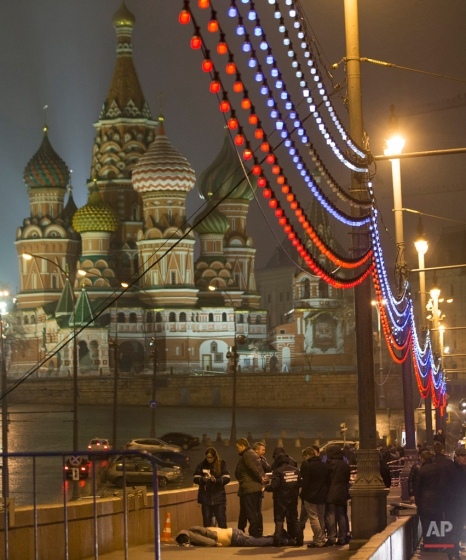 Russian police investigate the the body of Boris Nemtsov, a former Russian deputy prime minister and opposition leader at Red Square with St. Basil Cathedral in the background in Moscow, Russia, Saturday, Feb. 28, 2015. (AP Photo/Pavel Golovkin)