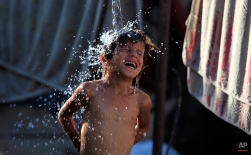 Naeema Abu Shaweesh, 30, showers her children outside their home in Gaza City, June 15, 2014. (AP Photo/Hatem Moussa)