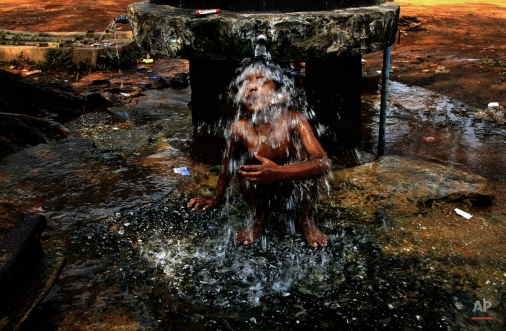 An Indian boy takes a bath under a roadside public water supply tap on a hot afternoon in the eastern Indian city of Bhubaneswar, India, Friday, March 27, 2015. Heat wave conditions prevailed as temperatures rise in costal parts of eastern India. (AP Photo/Biswaranjan Rout)
