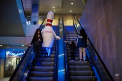 A person dressed as a bowling pin rides an escalator on Jan. 27, 2015, in Los Angeles. (AP Photo/Jae C. Hong)