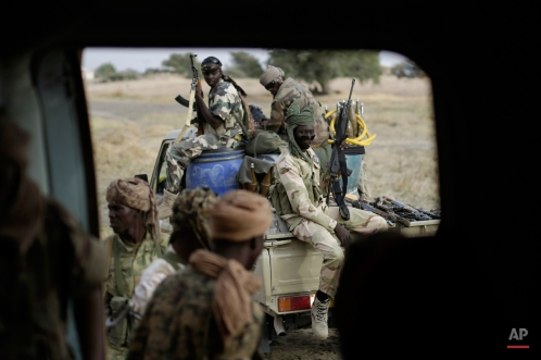 Chadian soldiers transfer weapons seized from Boko Haram fighters to a helicopter in the Nigerian city of Damasak, Nigeria, Wednesday, March 18, 2015. Damasak was flushed of Boko Haram militants last week, and is now controlled by a joint Chadian and Nigerien force. (AP Photo/Jerome Delay)