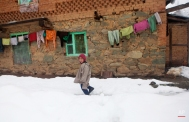 A Kashmiri boy walks in a snow-covered field outside his home in Mahen village, some 41 Kilometer (25 miles) northwest of Srinagar, Indian controlled Kashmir, Tuesday, March 17, 2015. The Jammu-Srinagar highway, connecting the Kashmir valley to the rest of the country, remained closed for the third consecutive day Tuesday following heavy rain and snowfall at some places. (AP Photo/Dar Yasin)