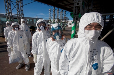 Workers in protective suits and masks wait to enter the emergency operation center at the crippled Fukushima Dai-ichi nuclear power station in Okuma, Japan on Nov. 12, 2011. (AP Photo/David Guttenfelder)