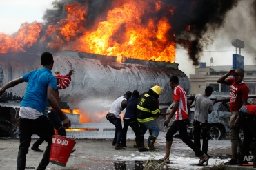 Firefighters try to contain a fire at a petrol station in Lagos, Nigeria on Thursday, March. 26, 2015. Witnesses said no one was injured in the fire that consumed a number of trucks and cars at the site. Authorities continue to investigate what caused the blaze. (AP Photo/Sunday Alamba)