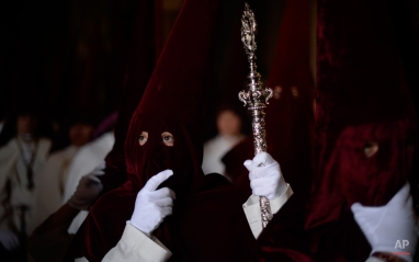 """Hooded penitents from""""La Veracruz"""" brotherhood wait inside of a church before start a Holy Week procession in Cordoba, Spain, Monday, March 30, 2015. Hundreds of processions take place throughout Spain during the Easter Holy Week. (AP Photo/Manu Fernandez)"""