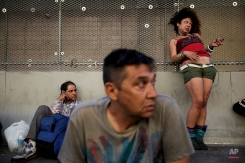 George Mendez, foreground, a 55-year-old recovering alcoholic, sits in front of a drunk woman in the Skid Row area of Los Angeles on July 23, 2013. The area, originally agricultural until the 1870s when railroads first entered Los Angeles, has maintained a transient nature through the years from the influxes of short-term workers, migrants fleeing economic hardship during the Great Depression, military personnel during World War II and the Vietnam conflict, and low-skilled workers with limited transportation options who need to remain close to the city's core, according to the Los Angeles Chamber of Commerce. (AP Photo/Jae C. Hong)