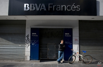 A man stands on the entrance of a bank during a transportation strike in Buenos Aires, Argentina, Tuesday, March 31, 2015. (AP Photo/Natacha Pisarenko)