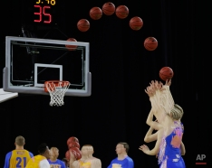 In this multiple exposure photo, UCLA's Thomas Welsh shoots a free throw during a practice session for a college basketball regional semifinal game in the NCAA Tournament, Thursday, March 26, 2015, in Houston. UCLA plays Gonzaga on Friday, March 27, 2015. (AP Photo/Charlie Riedel)