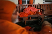 An Indian sadhu, or Hindu holy man, rests on a wooden bench inside an Ashram in Varanasi, India, Friday, Feb. 20, 2015. Varanasi is among the world's oldest cities, and millions of Hindu pilgrims gather annually here for ritual bathing and prayers in the Ganges river, considered holiest by Hindus. (AP Photo/ Rajesh Kumar Singh)