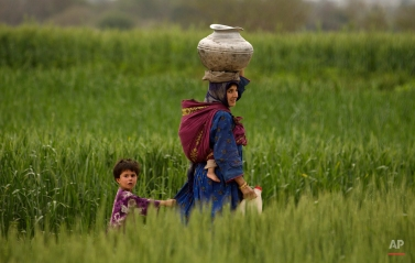 A Pakistani woman fetches clean water to her home in Islamabad's slums in Pakistan, Tuesday, March 24, 2015. There is a scarcity of fresh drinking water in Pakistan among a population of around 180 million. (AP Photo/B.K. Bangash)