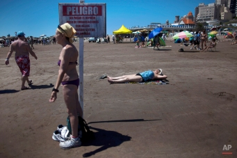 People spend time on the beach in Mar del Plata, Argentina, Wednesday, Jan. 9, 2013. Mar del Plata is a popular summer vacation spot for Argentines. The sign warns people to stay way from an area designated for boats with propellers. (AP Photo/Natacha Pisarenko)