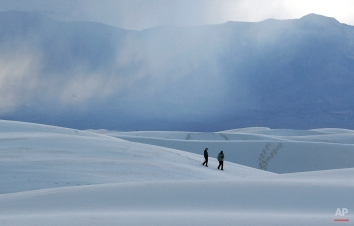 Visitors walk on a sand dune at dusk, Wednesday, March 4, 2015, in White Sands National Monument, N.M. (AP Photo/Patrick Semansky)