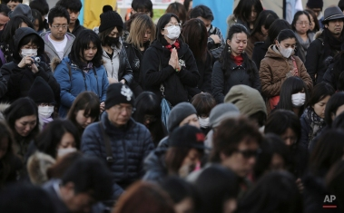 People observe a moment of silence at 2:46 p.m. during a special memorial event in Tokyo, Wednesday, March 11, 2015. Still struggling to recover, the tsunami-hit region of northeastern Japan marked the fourth anniversary of the disaster Wednesday with simultaneous moments of silence along the coast. (AP Photo/Eugene Hoshiko)