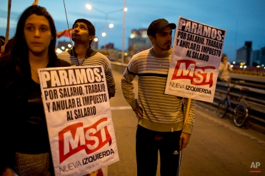 """Demonstrators holding posters with messages that read in Spanish; """"We strike for salary, work, and the annulment of the wage tax,"""" block a highway during a transportation strike in Buenos Aires, Argentina, Tuesday, March 31, 2015. (AP Photo/Natacha Pisarenko)"""