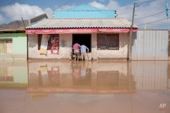 Two men stand in a flooded street at a shop in Copiapo, Chile, Thursday, March 26, 2015. Unusually heavy thunder storms and torrential rains that began on Tuesday have blocked roads, caused power outages and affected some 600 people on this normally dry region. (AP Photo/Pablo Sanhueza)