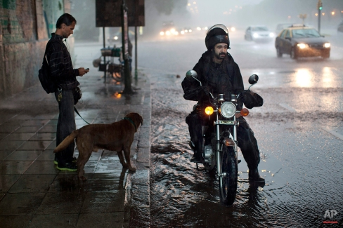People wait under a bridge to cover themselves from heavy rain in Buenos Aires, Argentina, Friday, Feb. 7, 2014. (AP Photo/Rodrigo Abd)