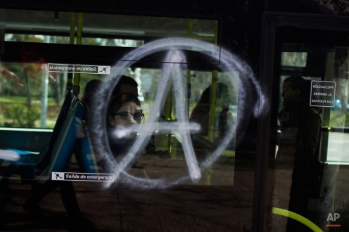 A woman looks through a bus window and in between an anarchist symbol, as part of the student strike graffiti at Complutense university campus in Madrid, Spain, Tuesday, March 24, 2015. Students and professors across Spain backed by trade unions are protesting changes in the system of university degrees with demonstrations and strikes. (AP Photo/Andres Kudacki)