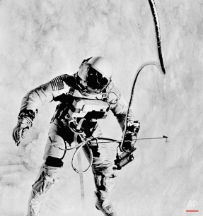 """Astronaut Ed White faces the Gemini 4 capsule during his 20-minute space """"walk"""" on June 8, 1965. In his right hand, White holds his oxygen space gun to maneuver around the capsule. A 35-mm camera is attached to the space gun. Astronaut James McDivitt took this photograph with a Hasselblad camera. (AP Photo/NASA/James McDivitt)"""