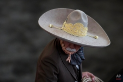 """In this Feb. 28, 2015 photo, a charro rides in the arena at the start of a roping event, during a charreada in Mexico City. Charreria is a sport that brings together enthusiasts and competitors of all ages. Charro Francisco Armando Juarez Manzur, 40, who was competing with the Nacional Charros Association team, said he's seen charros as old as 92 riding. But, he says, """"There are some tricks like bull riding, the pass of death, and wild mare riding, that are generally for someone younger, because the blows are very hard."""" (AP Photo/Rebecca Blackwell)"""