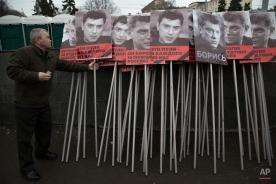 A man prepares portraits of opposition leader Boris Nemtsov who was gunned down on Friday, Feb. 27, 2015 near the Kremlin. (AP Photo/Pavel Golovkin)