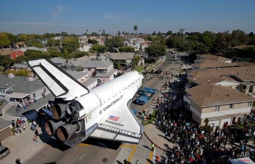 The Space Shuttle Endeavour slowly moves along city streets on a 160-wheeled carrier in Inglewood, Calif., Oct. 13, 2012. (AP Photo/Jae C. Hong)