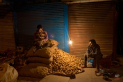 Indian vendors wait for early morning customers at the wholesale vegetable market in the old city area of New Delhi, India, Friday, Feb. 27, 2015. The government of Asia's third-largest economy is this week expected to present the budget for the fiscal year ending March 2016. (AP Photo/Bernat Armangue)