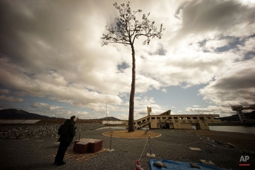 The lone pine tree that miraculously survived the deadly 2011 tsunami among 70,000 trees along the coastline, stands in Rikuzentakata, Iwate Prefecture, northeastern Japan on March 4, 2015. The tree, which was badly damaged from seawater after surviving the tsunami, was cut down in 2012 and treated for decay after which it was preserved using artificial materials. It was later placed back where it was found to stand as a symbol of hope and survival. (AP Photo/Eugene Hoshiko)