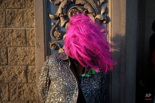 A homeless woman wears a wig while waiting for the start of a karaoke night outside a church in the Skid Row area of Los Angeles, May 15, 2013. (AP Photo/Jae C. Hong)
