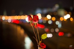 Red roses are at the place where Boris Nemtsov, a charismatic Russian opposition leader and sharp critic of President Vladimir Putin, was gunned down on Friday, Feb. 27, 2015 near the Kremlin, in Moscow, Russia, Monday, March 2, 2015. The investigation into the killing of Boris Nemtsov, a fierce critic of Russian President Vladimir Putin who was gunned down not far from the Kremlin, faced conflicting reports Monday about possible surveillance footage of his slaying. Words on a portrait reading 'Fight!' (AP Photo/Alexander Zemlianichenko)