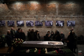 Relatives and friends pay their last respects while passing the coffin of Boris Nemtsov, a charismatic Russian opposition leader and sharp critic of President Vladimir Putin, during a farewell ceremony inside the Sakhavov's center in Moscow, Russia, Tuesday, March 3, 2015. (AP Photo/Pavel Golovkin)