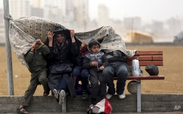 A Palestinian family covers themselves from rain at the Gaza port in Gaza City, Feb. 15, 2014. (AP Photo/Hatem Moussa)