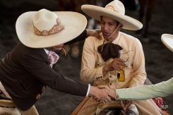 """In this Feb. 28, 2015 photo, charros drink and greet friends as they sit on horseback on the sidelines of a charreada in Mexico City. Although winning is always an honor, said Manuel Basurto Rojas, president of the National Charros Association, the main importance of the infrequent national competitions is really """"social harmony."""" """"It's primarily a chance to spend time with all the brotherhood of charreria from the entire Mexican republic."""" (AP Photo/Rebecca Blackwell)"""