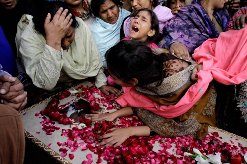 Family members of Pakistani Christian community mourn the death of a victim of Sunday's suicide bombings that struck two churches, in Lahore, Pakistan, Monday, March 16, 2015. Pakistan's minority Christians blocked roads Monday in protest over the bombings killing more than a dozen people in the latest attack against religious minorities in this increasingly fractured country. (AP Photo/K.M. Chaudary)