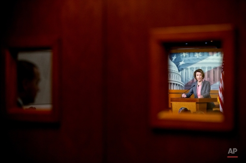House Minority Leader Nancy Pelosi of Calif. is seen though a window during her weekly news conference on Capitol Hill in Washington, Thursday, March 26, 2015. (AP Photo/Andrew Harnik)