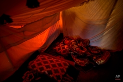 Syrian refugee child Shaikhah Elaiwi, 1, sleeps on the ground of her family's tent at an informal tented settlement near the Syrian border, on the outskirts of Mafraq, Jordan, Monday, March 16, 2015. (AP Photo/Muhammed Muheisen)