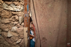 A boy peeks through a curtain at the doorway of a madrassa, a school for the study of Islam, while children attend their daily class, on the outskirts of Islamabad, Pakistan, Saturday, Feb. 21, 2015. (AP Photo/Muhammed Muheisen)
