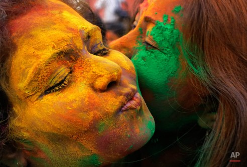 Students at the Rabindra Bharati University, named after Indiaís first Noble laureate Rabindra Nath Tagore, hug each other as they play with colors ahead of spring festival Holi in Kolkata, India, Monday, March 2, 2015. (AP Photo/ Bikas Das)