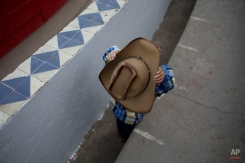 In this Feb. 26, 2015 photo, a boy adjusts his cowboy hat as he waits in the front row for the start of a charreada at the National Charros Association arena in Mexico City. (AP Photo/Rebecca Blackwell)
