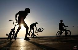 Cyclists perform a stunt by the shores of the Arabian Sea in Mumbai, India, Thursday, Feb 19, 2015.(AP Photo/Rafiq Maqbool)