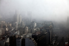 Seen through a window, fog hovers over buildings in downtown Buenos Aires, Argentina, early Monday, July 29, 2013. A heavy morning fog covering Buenos Aires forced flight delays at local airports around Argentina. (AP Photo/Natacha Pisarenko)