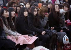 People mourn for victims of the March 11, 2011 earthquake and tsunami during a special memorial event in Tokyo, Wednesday, March 11, 2015. Still struggling to recover, the tsunami-hit region of northeastern Japan marked the fourth anniversary of the disaster Wednesday with simultaneous moments of silence along the coast. (AP Photo/Eugene Hoshiko)